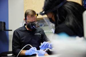 Hilliard dentist Dr. Phil Chahine performing periodontal disease treatment on a Columbus patient sore, inflamed gums.